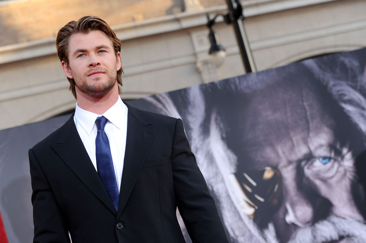 Chris Hemsworth in front of a Thor movie banner