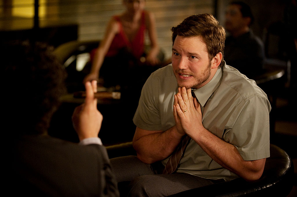 Chris Pratt as Andy is pleading with someone. His hands are folded as he sits across from an unknown person.
