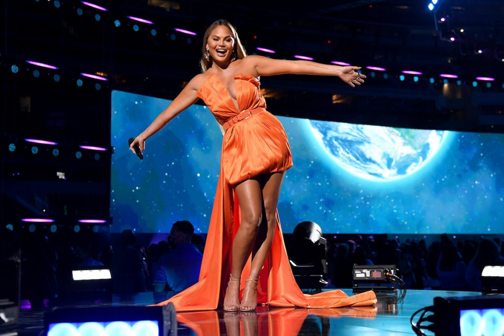 Chrissy Teigen wears an orange dress and strikes a pose with open arms on stage.