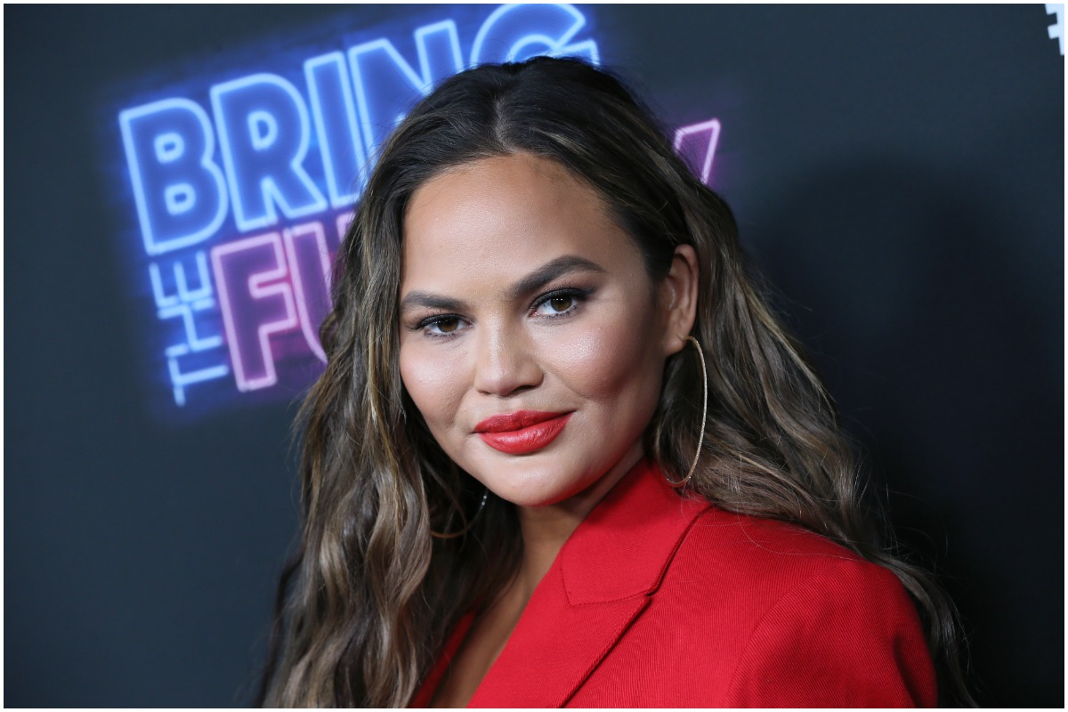 Chrissy Teigen smirking at the camera at a red carpet event.