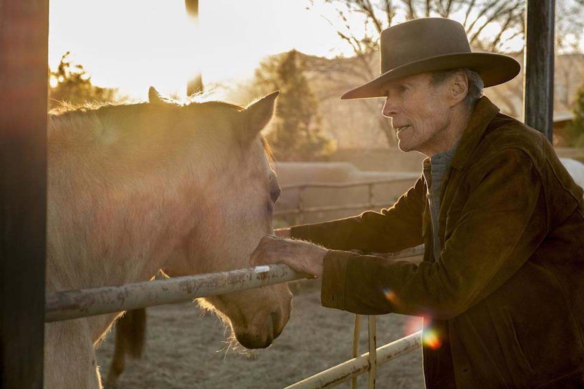 Clint Eastwood on the set of 'Cry Macho.' He wears a cowboy hat and brown suede jacket while leaning against a fence. A blonde-haired horse is on the other side of the fence and the sun is shining bright behind them. 'Cry Macho,' out Sept. 17, marks Eastwood's first western since 1992's 'Unforgiven,' and it required him to ride a horse for the first time since filming 'Unforgiven' three decades ago.