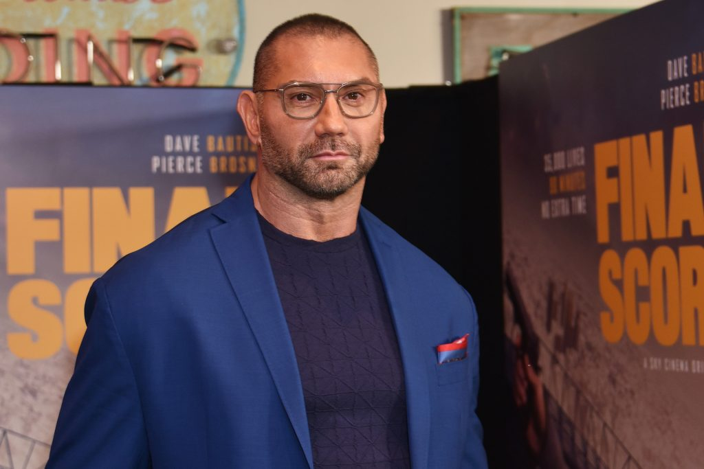 Dave Bautista smiling in front of a blurred background
