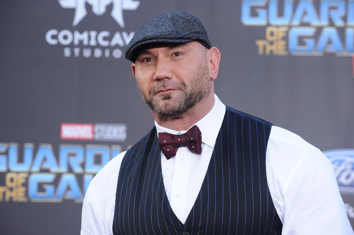 Marvel star Dave Bautista does not reprise his role in 'What If...?' In this photo, he's wearing an ivy cap, black striped vest, white shirt, and bowtie. He's looking past the camera and there's a 'Guardians of the Galaxy' wall behind him.