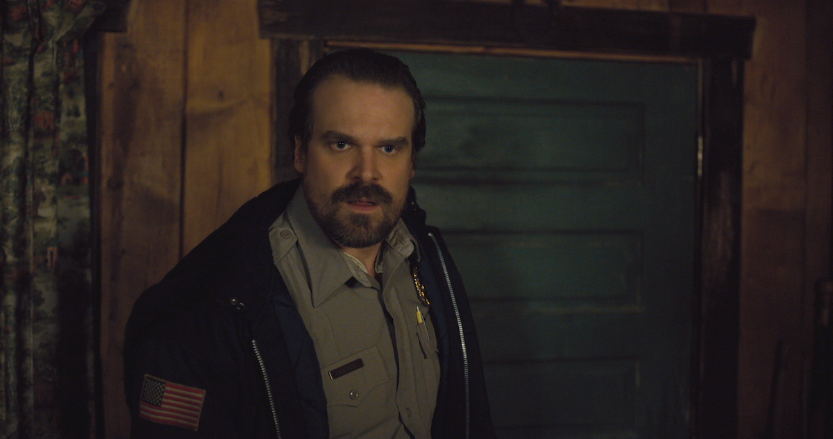 David Harbour in his police uniform looking shocked in a production still from Stranger Things Season 2.