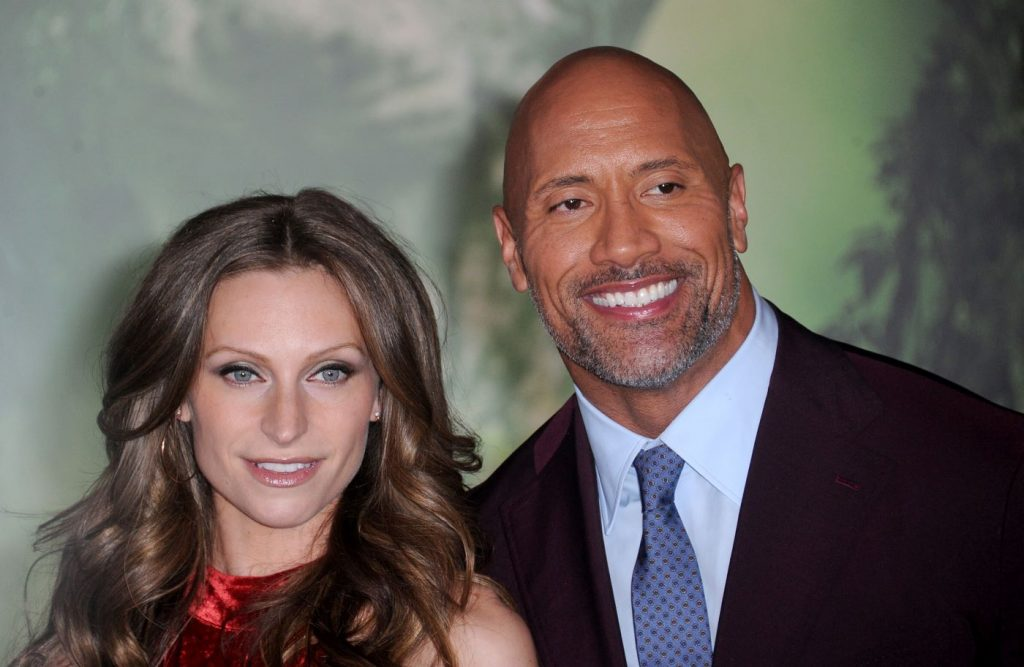 Dwayne Johnson and wife Lauren Hashian dressed professionally in front of a green background.