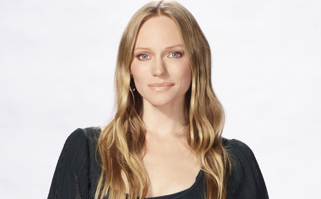 Days of Our Lives star Marci Miller is pictured here in a black scooped neck shirt against a white background