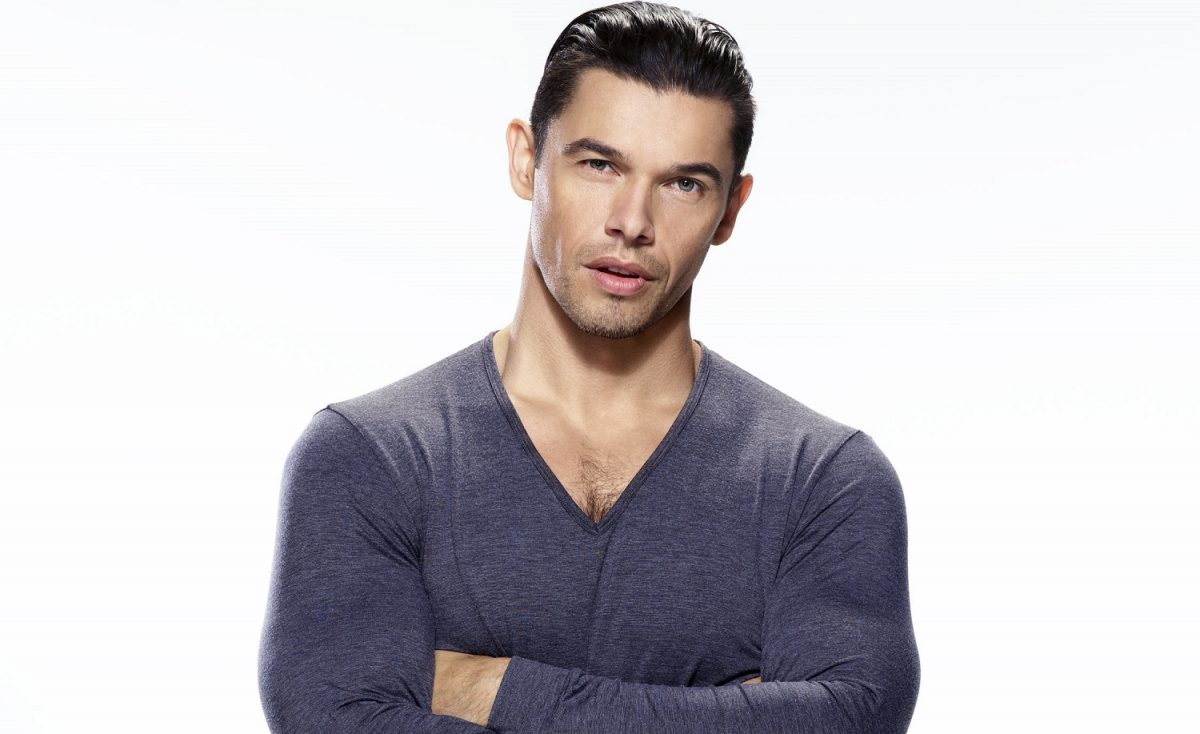 Days of Our Lives speculation has Xander, played by Paul Telfer, pictured here in a blue long sleeved shirt against a white backgroundf