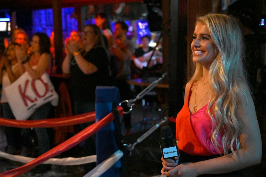 Demi Burnett holds a microphone while participating on 'The Bachelor'. She's wearing a red dress and her long, blonde hair is down.