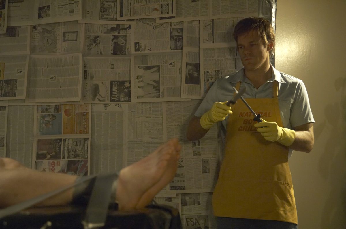 Michael C. Hall as Dexter stands in his kill room sharpening a knife. He is wearing an apron and gloves and looking at the feet of someone wrapped to his kill table.