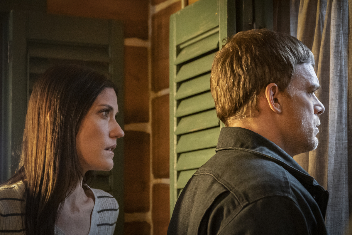 Dexter looks out the window wearing a brown jacket and Deb stands behind him wearing a striped top.