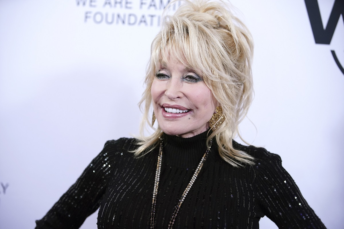 Dolly Parton in a black dress and gold jewelry.