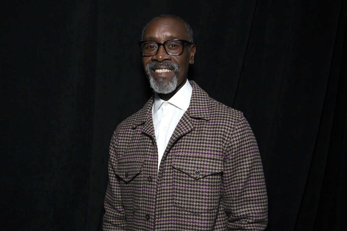 Don Cheadle smiling in front of a black background