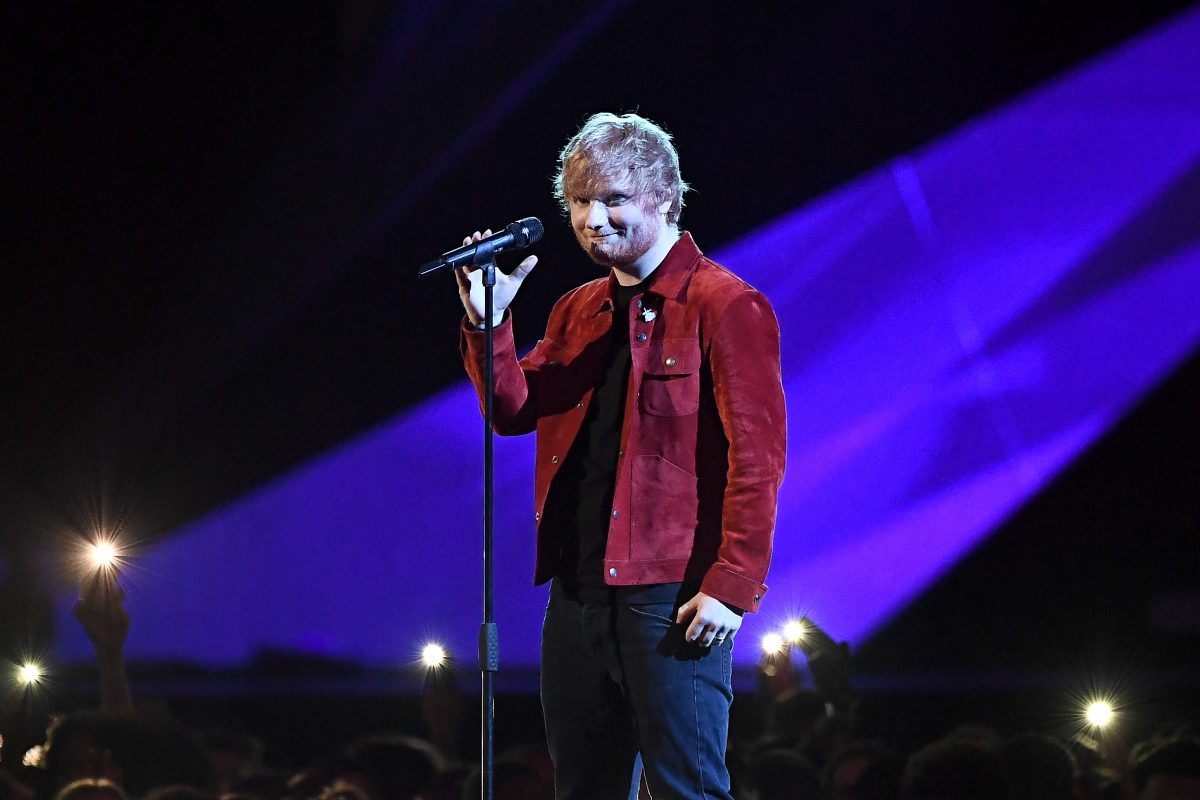 Ed Sheeran in a red jacket on stage at an awards show.