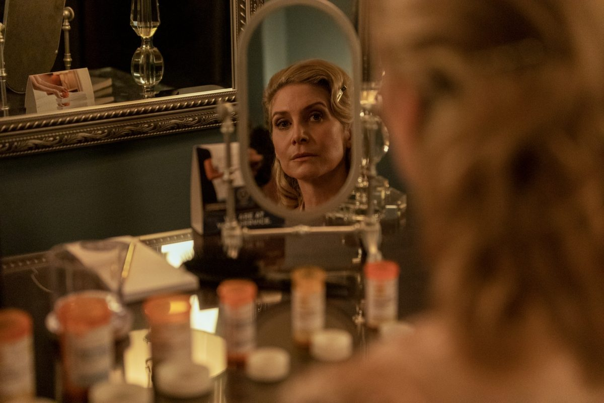 Carla Limbrey, played by Elizabeth Mitchell, looking into a vanity mirror in the Netflix series 'Outer Banks'