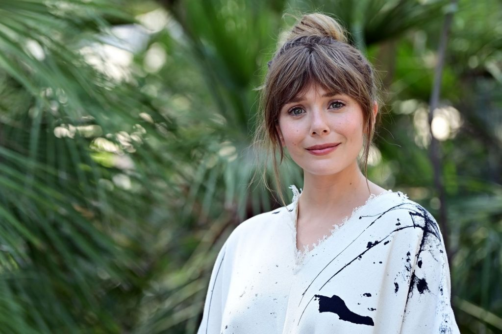 Elizabeth Olsen in a white shirt with black splotches in front of a background with green foliage.