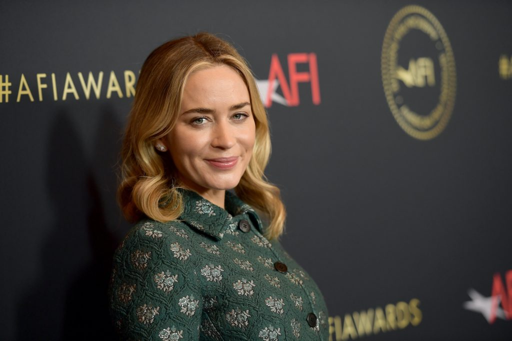 Emily Blunt smiling in front of a black background