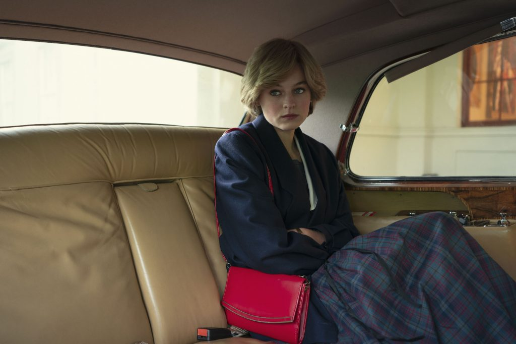 Emma Corrin sitting in the back of a car in 'The Crown.'