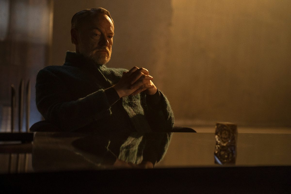 Foundation star Jared Harris sits with his hands folded on a table