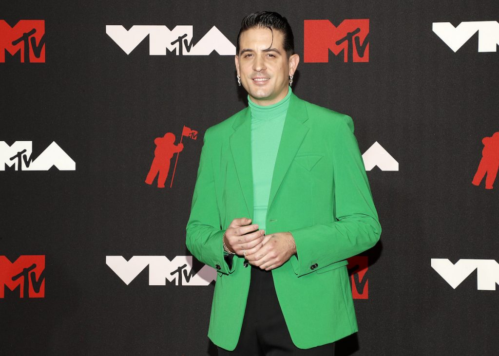 G-Eazy wearing a bright green jacket and matching turtleneck at the 2021 VMAs.