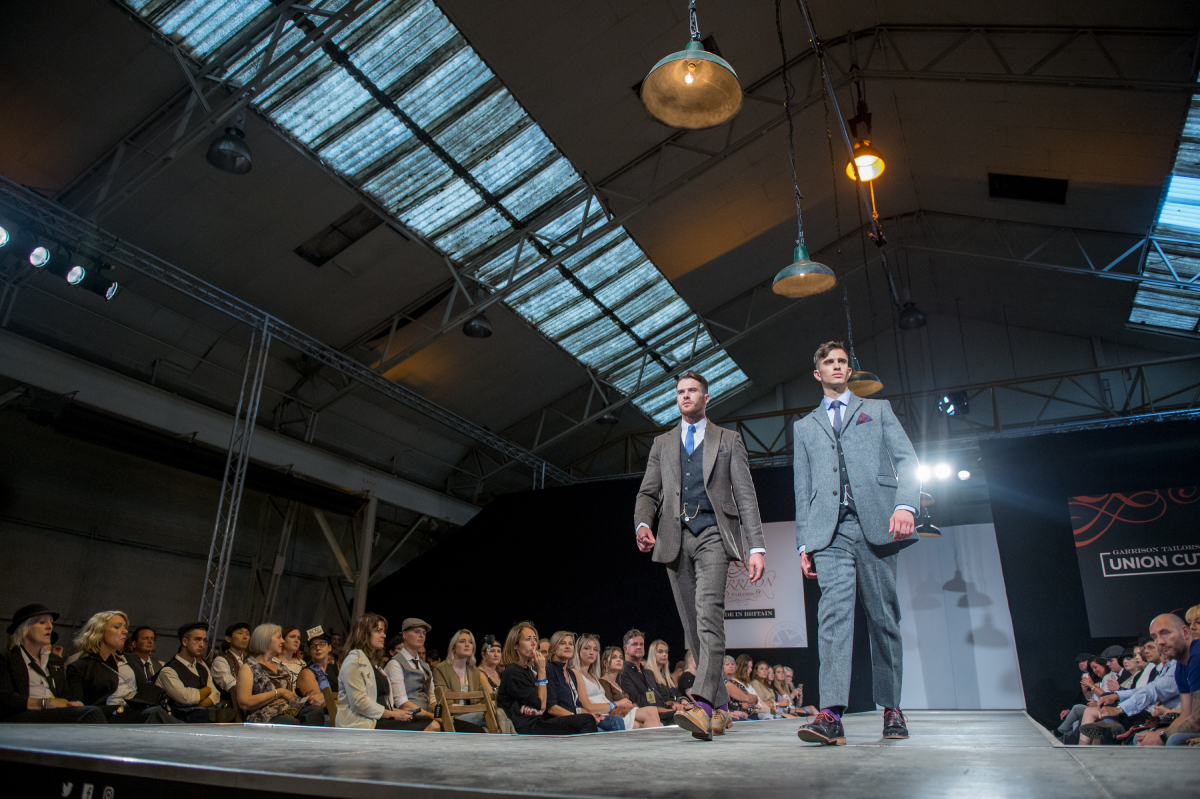 Two men model their 'Peaky Blinders' style three-piece suits at a fashion show.