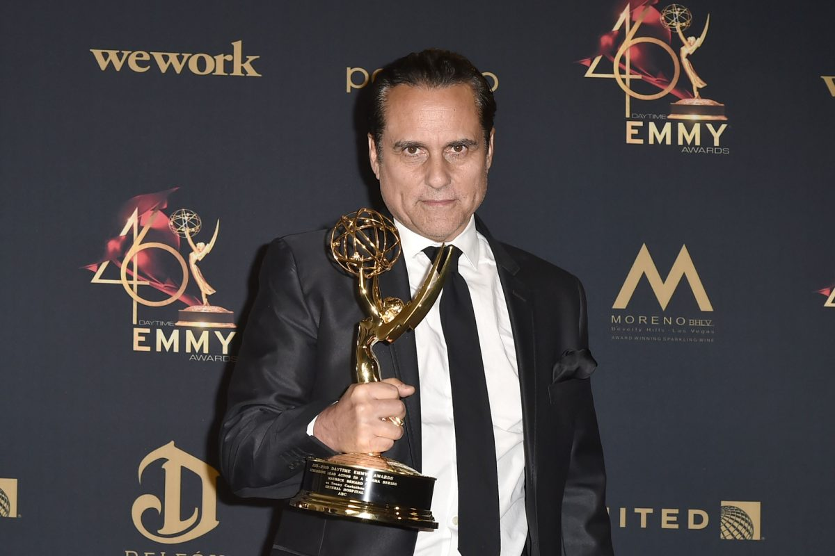 General Hospital star Maurice Benard is pictured here holding a Daytime Emmy while wearing a black suit and a purple collared shirt