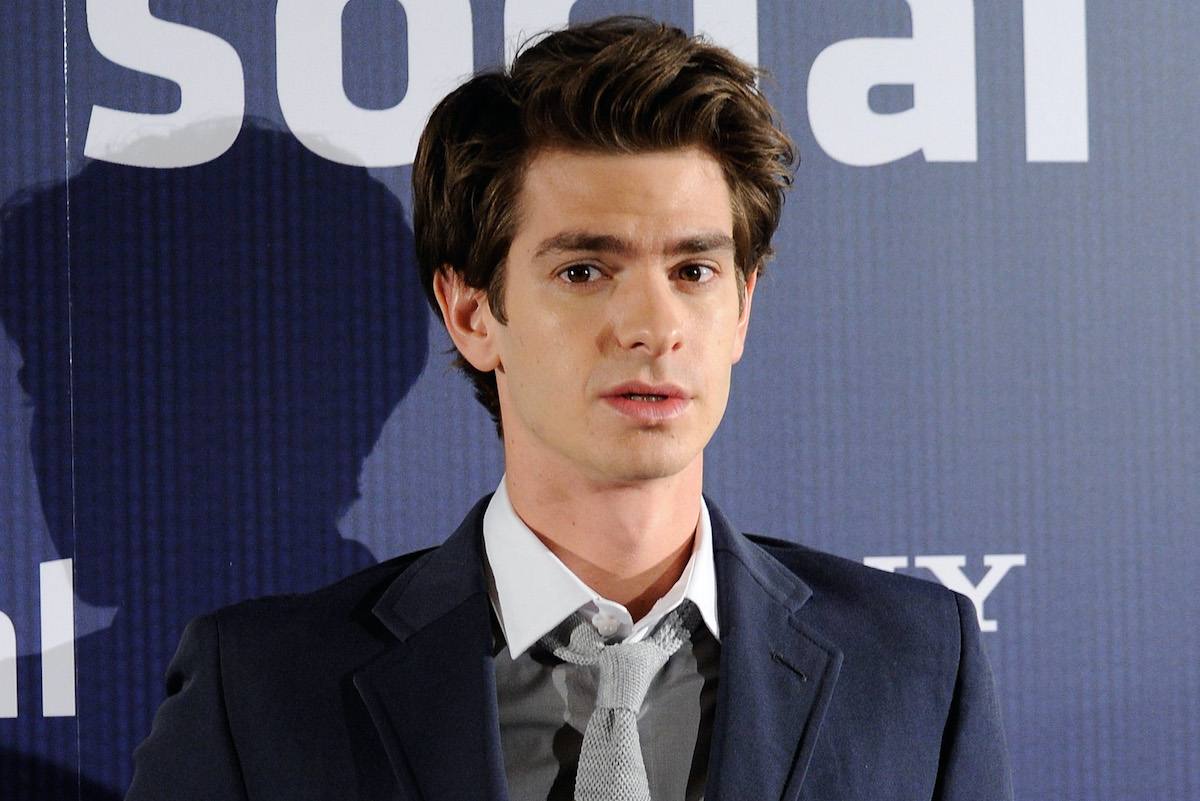 Andrew Garfield at a photocall for 'The Social Network' in 2010. He wears a navy blue suit, grey vest, and light grey tie as he stands in front of a similarly navy blue backdrop that says 'social' and 'Sony' in white lettering. Garfield's 'lawyer up' scene in 'The Social Network' is still one of the most famous from the movie. He revealed what it was like to film it with director David Fincher in a recent interview.