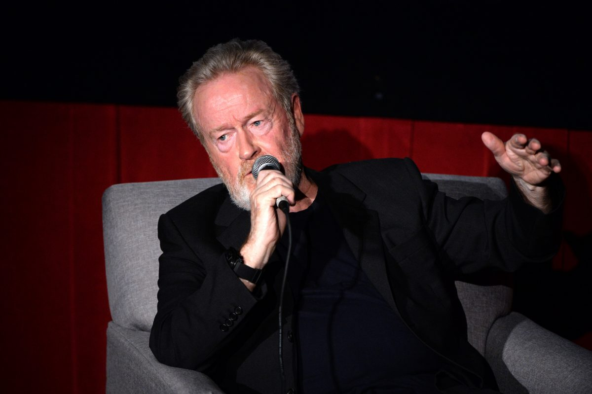 Ridley Scott speaks into a microphone while wearing a black jacket and sitting in a gray chair.