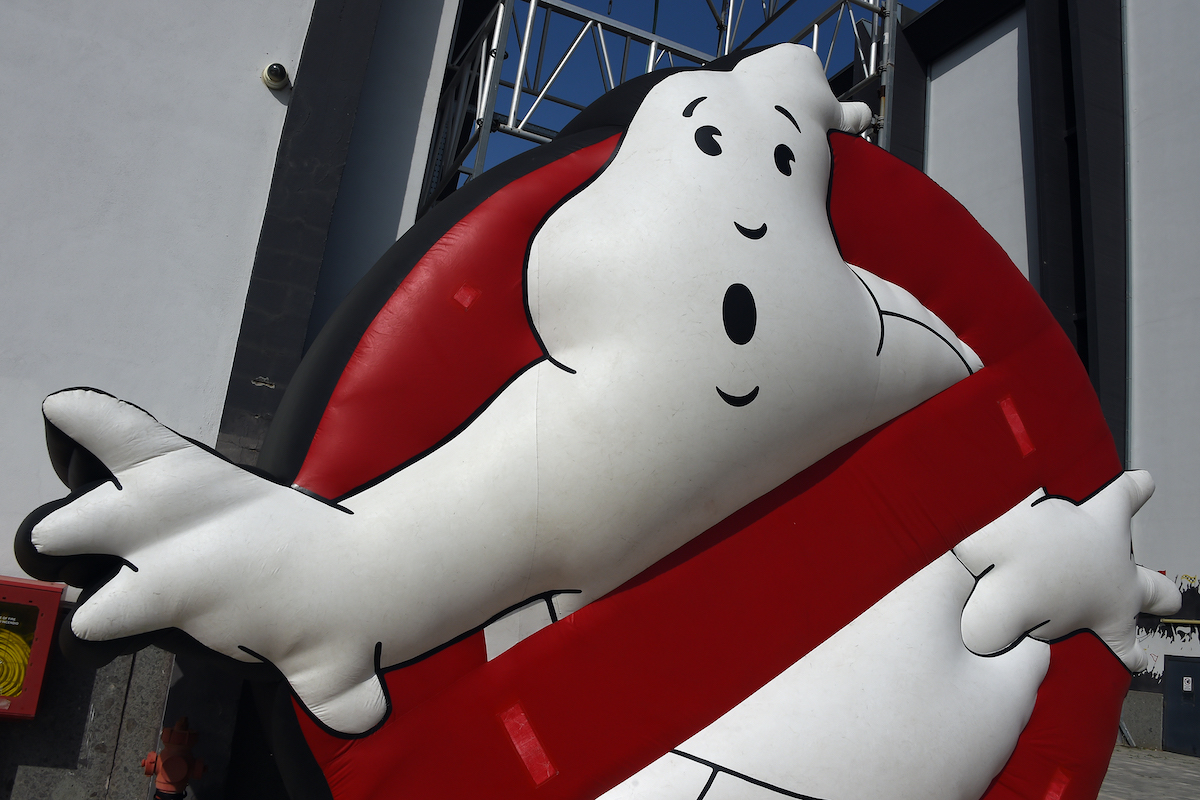 The 'Ghostbusters' logo with a white ghost peeking through a red circle.