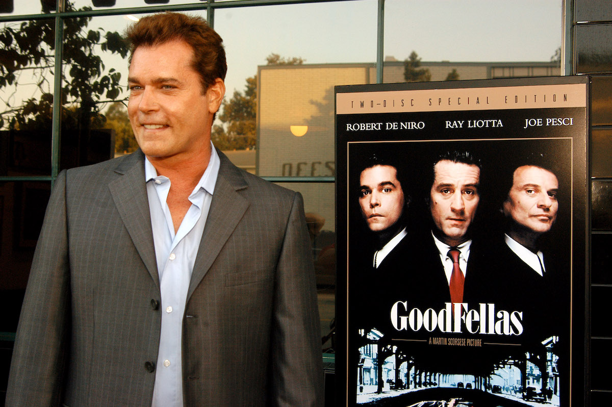 Ray Liotta standing next to a poster of 'Goodfellas'