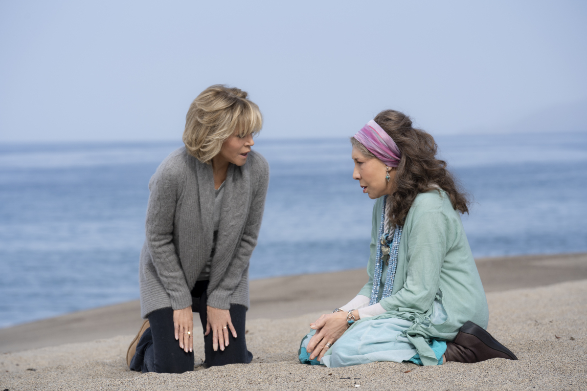 Grace and Frankie kneel sit in the sand on the beach.