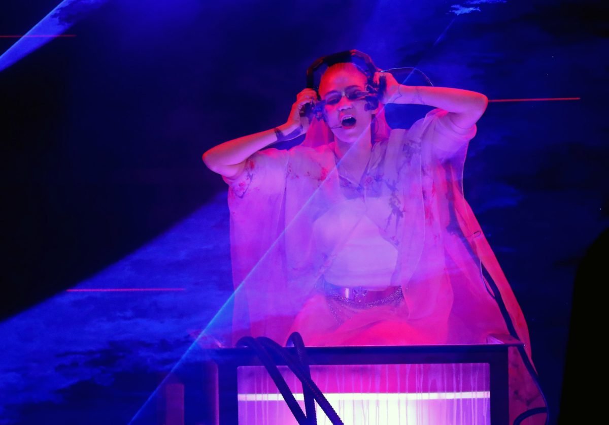 Grimes performs with headphones on