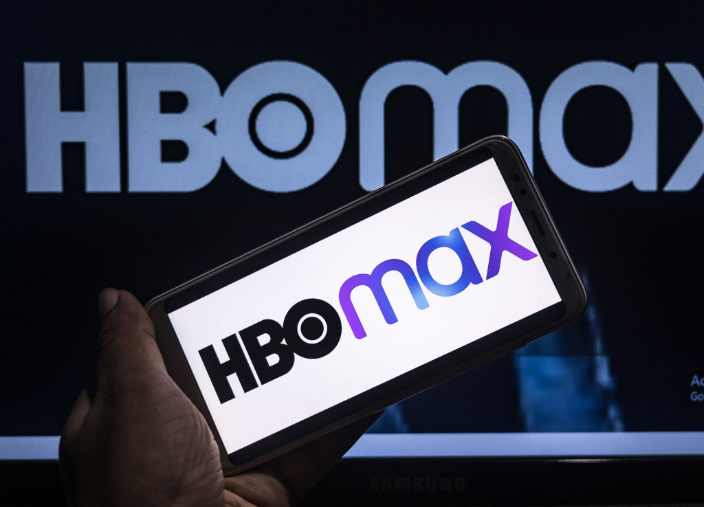 HBO Max logo on a phone screen in front of a poster.