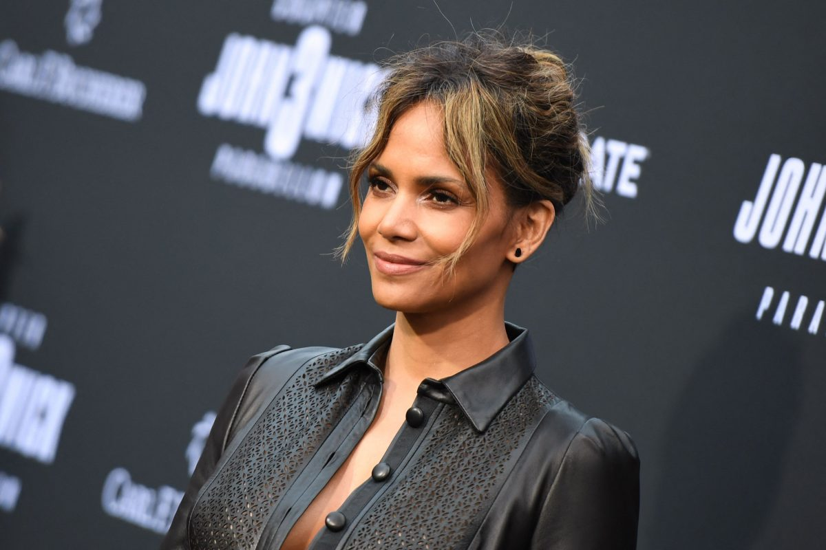 Halle Berry in a black buttoned shirt posing with her side toward the camera at the premiere of 'John Wick: Chapter 3 - Parabellum' in 2019.
