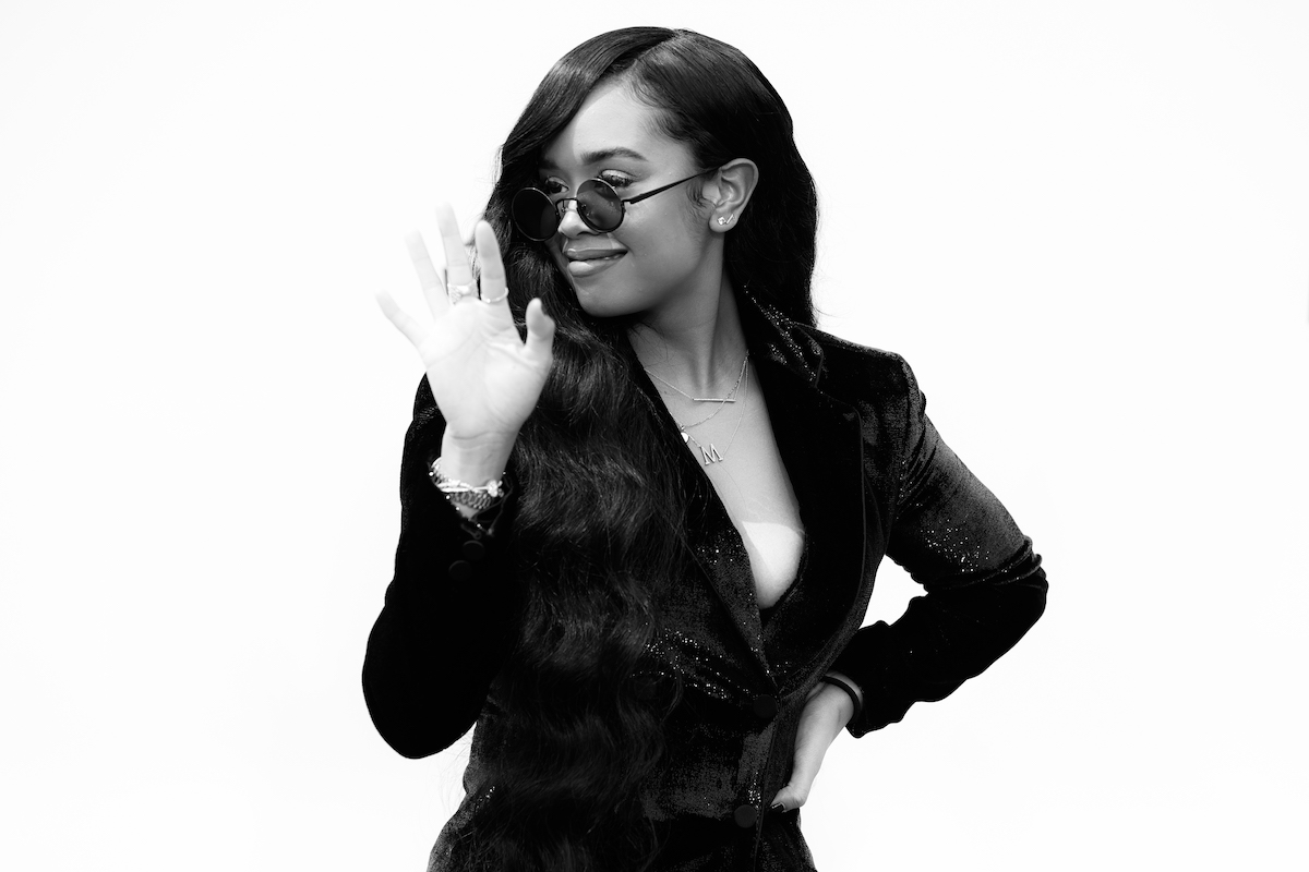 H.E.R. smiling and waving while wearing sunglasses.