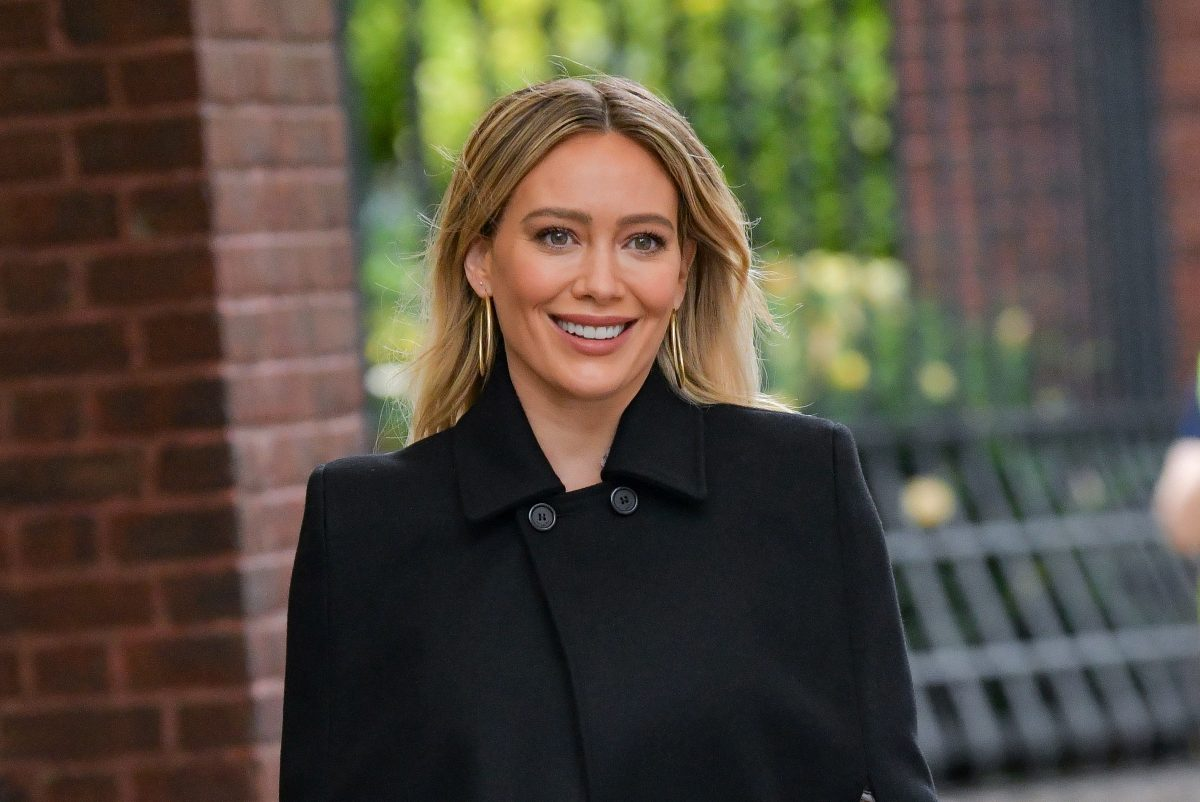 Hilary Duff in a black coat from the chest up.