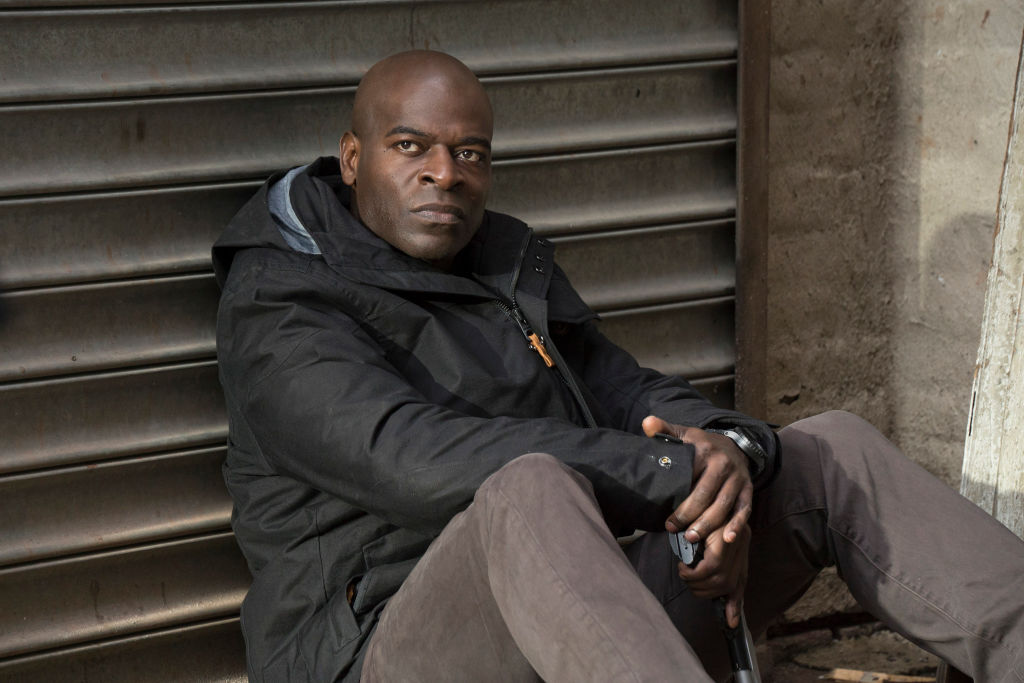 Hisham Tawfiq as Dembe Zuma sits with his back against a wall with an angry look on his face. He's dressed in a puffy black coat and grey pants.