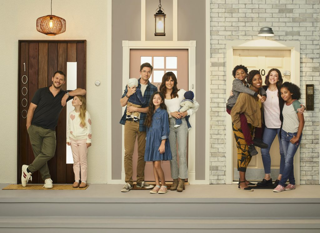 Cast of 'Home Economics' in front of a set of doors in a promo photo