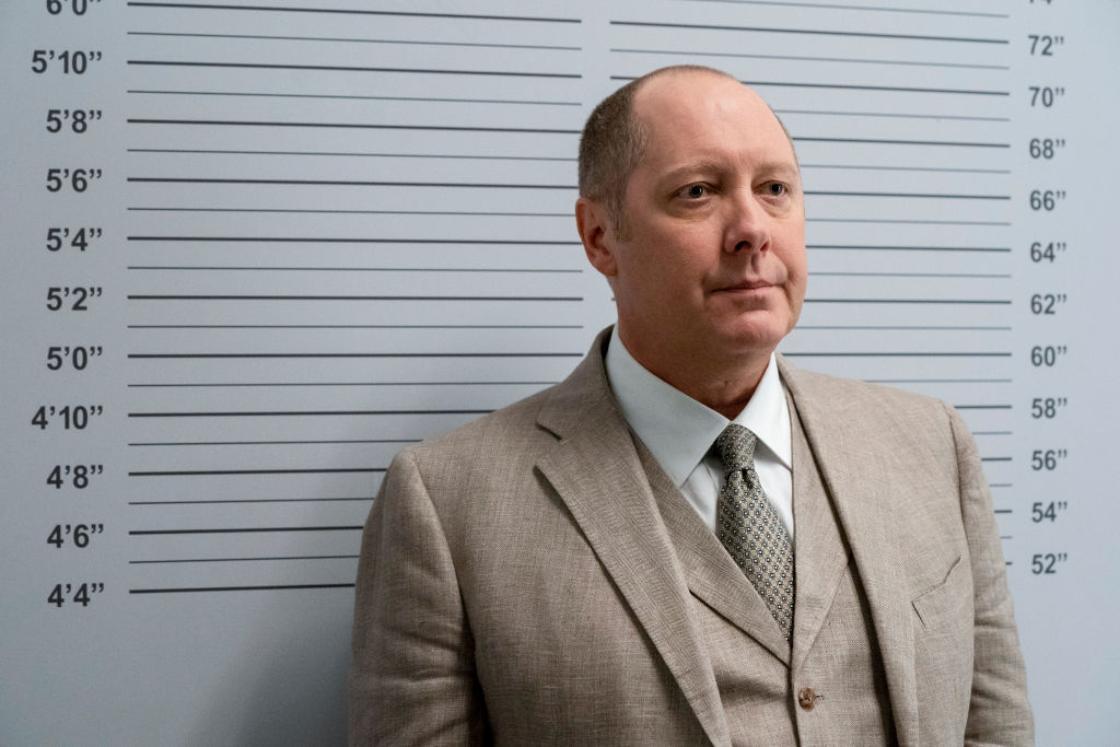 James Spader as Raymond 'Red' Reddington stands in a police lineup for a photo. He's wearing a tan suit.