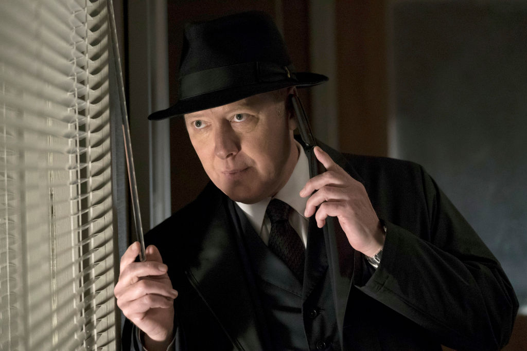 James Spader as Raymond 'Red' Reddington peers out the window while speaking on a phone.