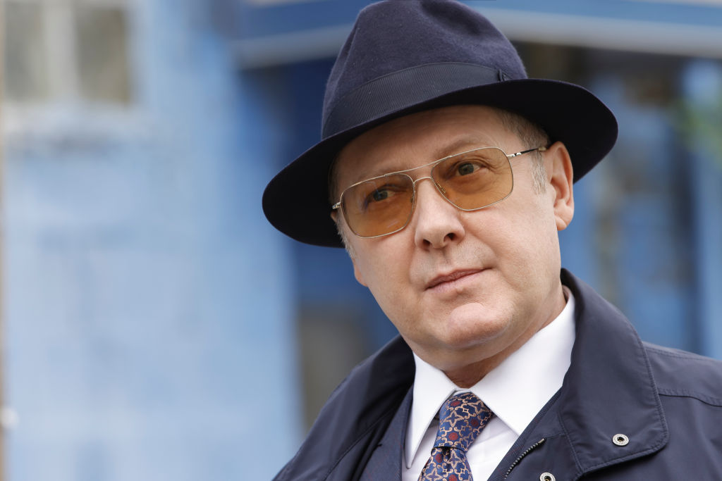 James Spader as Raymond 'Red' Reddington is wearing a navy fedora and matching coat with sunglasses.