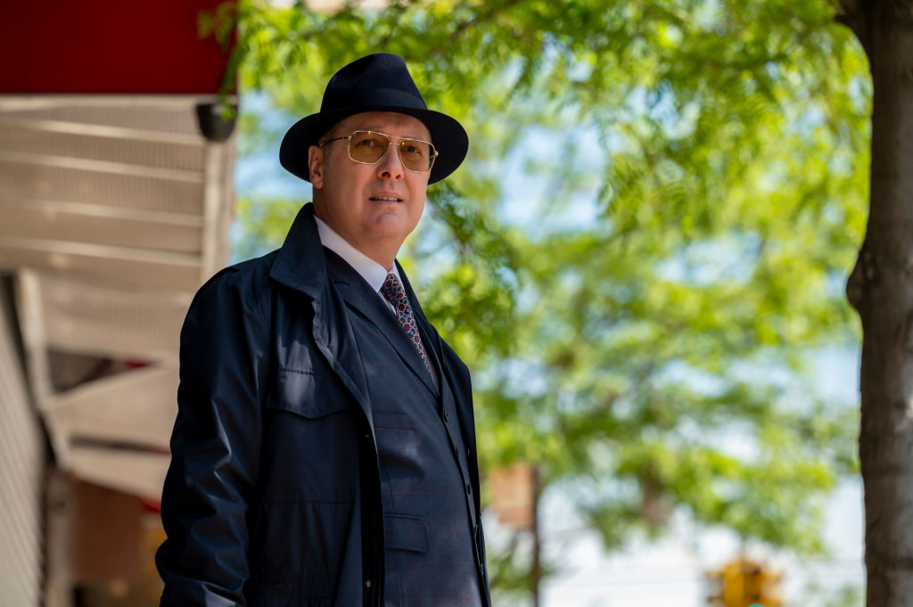'The Blacklist' Season 9 star James Spader as Raymond 'Red' Reddington is dressed in a navy suit with matching trench coat and fedora as he peers through his sunglasses while standing outside.