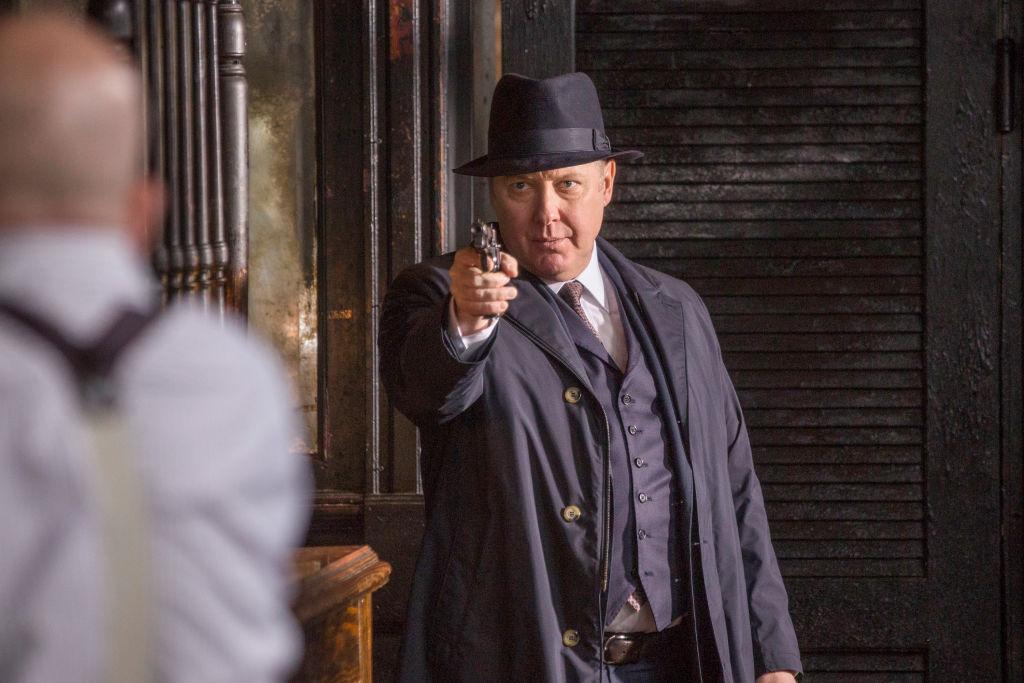 James Spader as Raymond 'Red' Reddington points a gun at Ian Garvey.