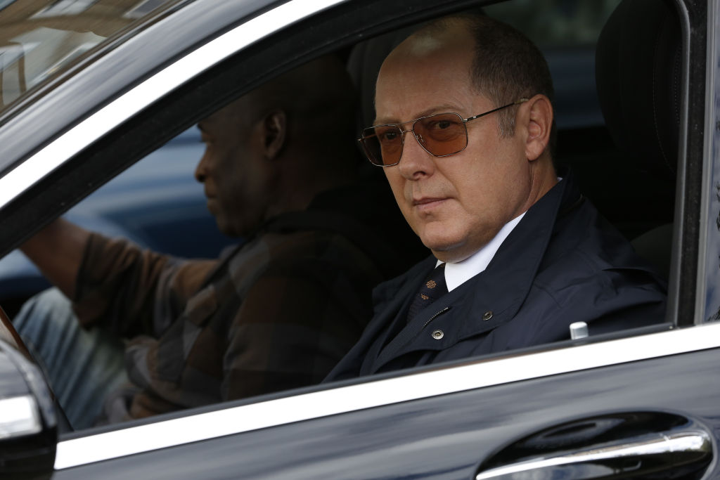 Hisham Tawfiq as Dembe Zuma, James Spader as Raymond 'Red' Reddington sit in a car.