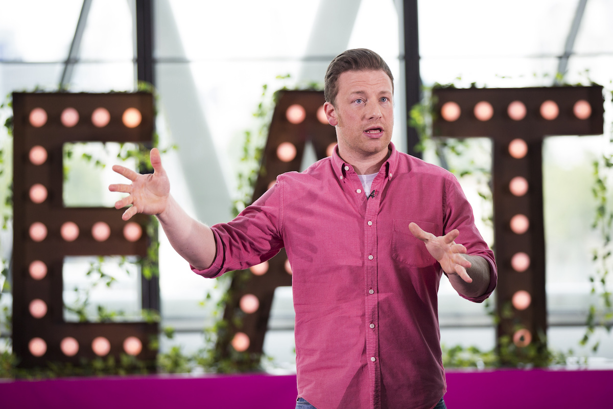Jamie Oliver speaks while wearing a pink button down shirt during Jamie Oliver Presents Food Revolution Day in 2014