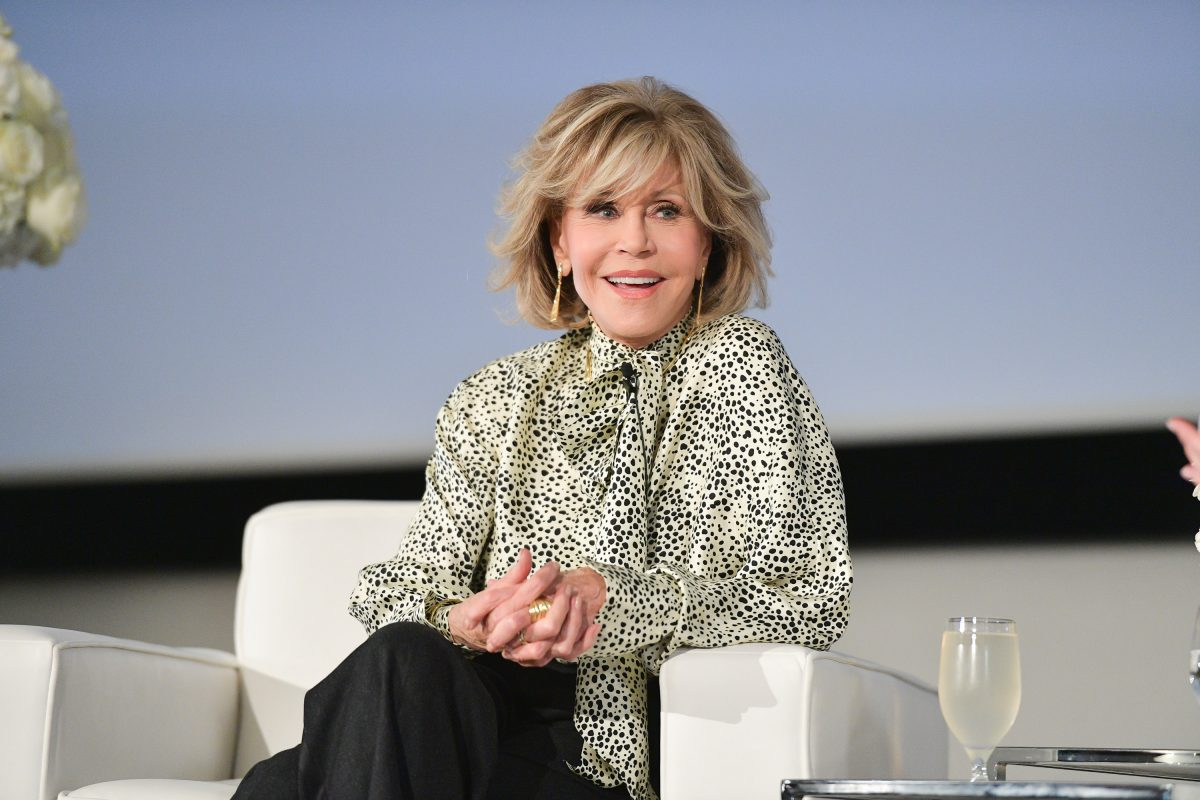 Jane Fonda smiles and sits in a chair. She is wearing a cream colored top with black polka dots and black pants.
