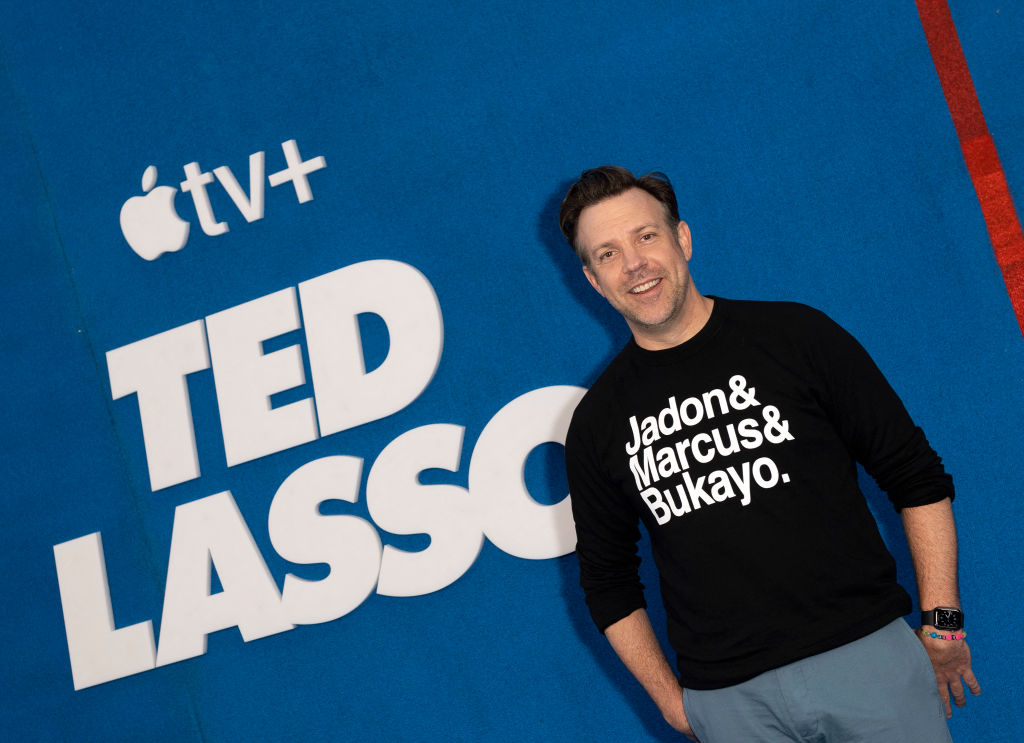 Jason Sudeikis walks the red carpet while wearing a black t-shirt. A 'Ted Lasso' poster is behind him.