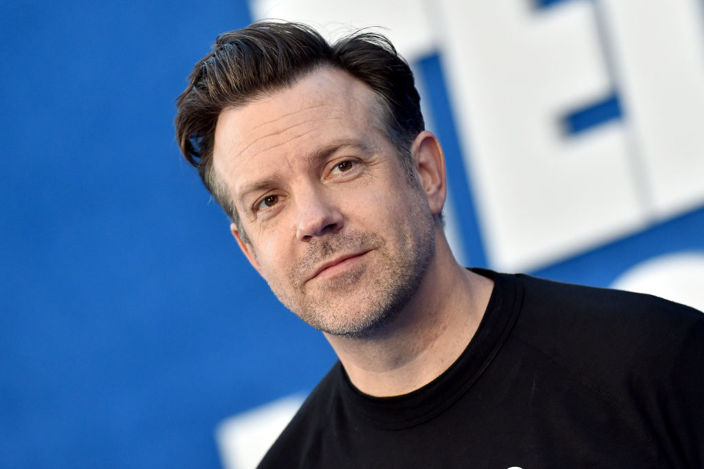 Jason Sudeikis poses on the red carpet in a black t-shirt with a blue backdrop that says 'Ted Lasso'.