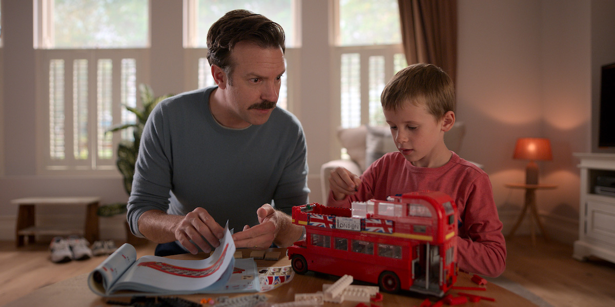 Jason Sudeikis watches as Gus Turner assembles a red double decker bus in 'Ted Lasso'