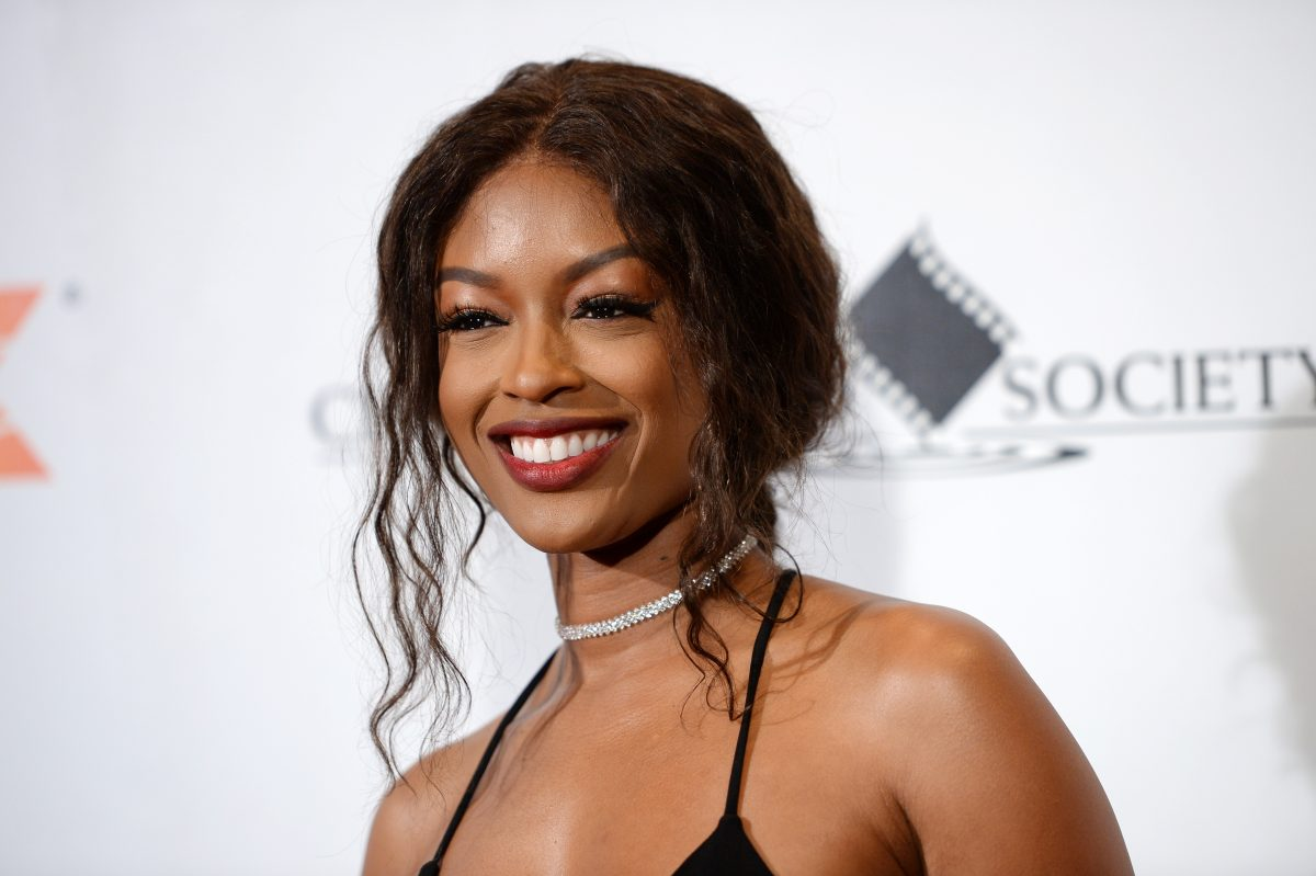 'Batwoman' star Javicia Leslie. She's wearing a black tank and her hair is pulled back. Several curls fall in front of her face. She's smiling, and she stands in front of a white wall with words on it.
