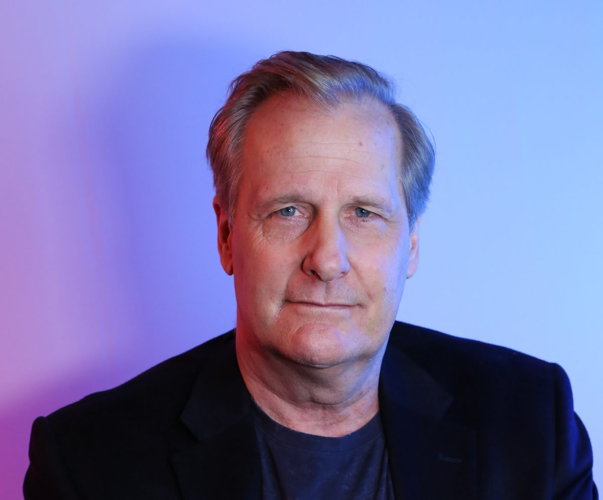 Jeff Daniels of the 'American Rust' cast slightly smiling in a head shot against a blue/purple background